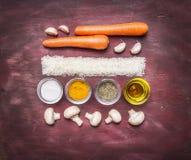 烹调素食食物的概念排行了在木土气背景的长方形红萝卜米大蒜黄油蘑菇各种各样的调味料 免版税库存图片
