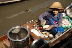 烹调en的妇女卖汤面在浮动市场曼谷上 图库摄影
