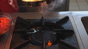 烹调flambe在平底锅的无法认出的厨师样式盘在餐馆现代厨房里  混合专业的厨师和 股票录像