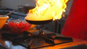 烹调flambe在平底锅的男性厨师样式盘在餐馆现代厨房里  油煎专业的厨师扔和 股票视频