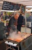 烹调Kebabs的人在岩石星期六早晨市场上 免版税库存照片