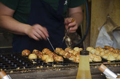 烹调takoyaki的日本人是一顿球形的日本快餐 库存照片