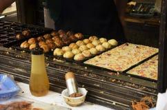 烹调takoyaki的日本人是一顿球形的日本快餐 免版税库存照片