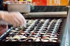 烹调takoyaki的日本厨师是一顿球形的日本快餐f 图库摄影