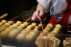 烹调takoyaki的日本厨师是一顿球形的日本快餐f 免版税库存照片