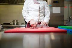 烹饪专业厨师切口和准备肉盘纤巧 餐馆和旅馆厨师,烹饪服务,承办宴席 免版税库存照片