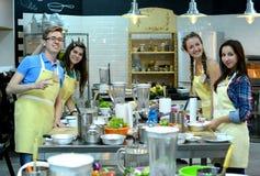 烹饪课 年轻愉快的朋友在厨房里 免版税库存图片
