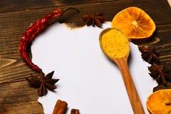 烹饪食谱概念 香料,厨房草本在白皮书附近放置 肉桂条、干桔子和八角位置 库存图片