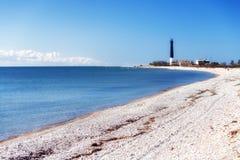 黑烽火台蓝色海和白色石头 免版税库存图片