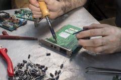 焊剂焊接的焊剂集成电路 一位焊接的战士的手有焊铁的 库存照片