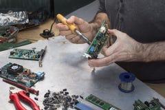 焊剂焊接的焊剂集成电路 一位焊接的战士的手有焊铁的 免版税库存照片