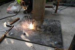 焊工与电极一起使用在电弧焊接在建筑坐 库存照片