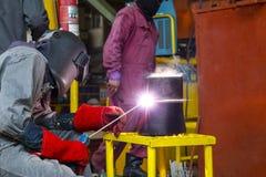 焊工人焊接减少管子 库存照片