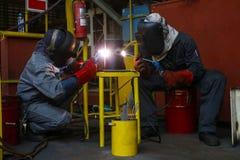 焊工人焊接缝管子 免版税库存照片