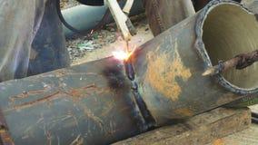 焊工使用电弧焊接在站点的管子金属。 股票视频