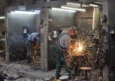 焊工在一家工业公司-钢组分的生产中运转 库存照片