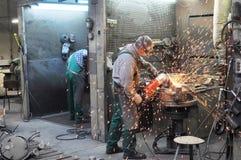 焊工在一家工业公司-钢组分的生产中运转 免版税库存图片