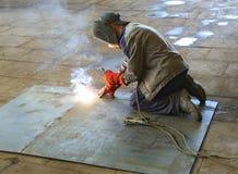 焊工在工厂 工作者焊接一张钢片 免版税库存图片