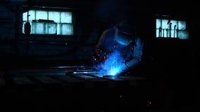 焊工在慢动作的一个面具运转 火花飞行用不同的方向 蓝色颜色焕发焊接 与钢一起使用 影视素材