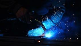 焊工在慢动作的一个面具运转 火花飞行用不同的方向 蓝色颜色焕发焊接 与钢一起使用 股票视频