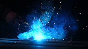 焊工在慢动作的一个面具运转 火花飞行用不同的方向 蓝色颜色焕发焊接 与钢一起使用 股票录像