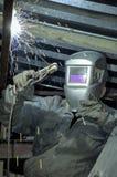 焊工在活梯做被焊接的工作在站立在屋顶下的屋子里 库存照片