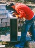焊工在金属电镀电弧焊接上把缝放 免版税库存照片
