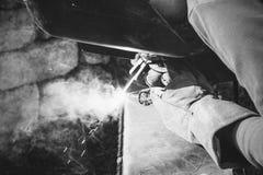 焊工在金属电镀电弧焊接上把缝放 免版税图库摄影