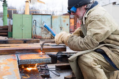 焊工工作者切口与吹管火炬的金属板 免版税图库摄影