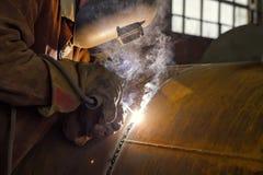 焊工执行焊接的大直径管子 免版税图库摄影