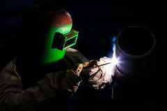 焊工有盾金属电弧焊接的资格管子 免版税库存照片