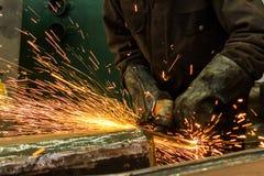 焊工焊接金属在有火花的车间 免版税库存图片