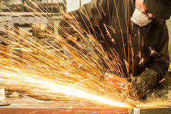 焊工焊接金属在有火花的车间 免版税库存照片
