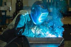 焊工焊接金属在防护套服分开 图库摄影