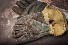 焊工的老皮手套在生锈的桌上 免版税库存照片