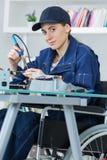 焊接电子线路的轮椅的女性技术员 免版税库存图片
