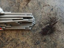 焊条和金属在肮脏的地面拂去灰尘 免版税库存照片