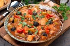 焖鱼用在西红柿酱的橄榄在板材 免版税库存图片