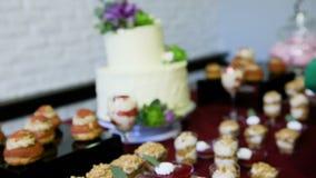 焦点在用在棒棒糖桌上的花装饰的白蛋糕 股票视频