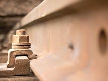 焦点的有选择性的领域 生锈的螺丝和坚果细节在老铁轨 具体领带 图库摄影