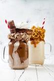 焦糖和巧克力疯狂的freakshake、奶昔用brezel奶蛋烘饼,玉米花、蛋白软糖、冰淇凌和打好的奶油 库存图片