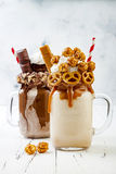 焦糖和巧克力疯狂的freakshake奶昔用brezel奶蛋烘饼、玉米花、蛋白软糖、冰淇凌和打好的奶油 库存照片