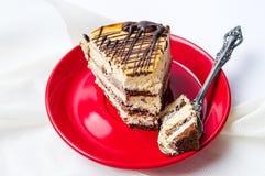 焦糖在红色板材的巧克力蛋糕切片 图库摄影