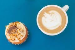 焦糖坚果杯形蛋糕和咖啡在桌上的 顶视图 库存图片