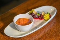 焦糖奶油用在白色板材供食的热的森林果子在现代餐馆,美食术的产品摄影 图库摄影