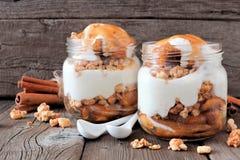 焦糖烘烤了在金属螺盖玻璃瓶的苹果冷甜点在土气木头 免版税图库摄影