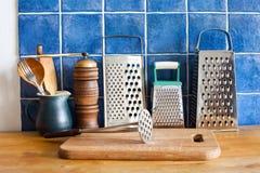 仍然厨房生活 葡萄酒器物 厨具磨丝器,陶瓷水罐,匙子 切板 蓝色瓦片墙壁 木 免版税库存照片