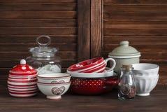 仍然厨房生活 葡萄酒陶器-瓶子面粉,陶瓷碗,平底锅,上釉了瓶子,调味汁瓶 在一张黑褐色木桌上 库存图片