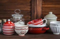 仍然厨房生活 葡萄酒陶器-瓶子面粉,陶瓷碗,平底锅,上釉了瓶子,调味汁瓶 在一张黑褐色木桌上 免版税库存图片