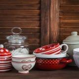 仍然厨房生活 葡萄酒陶器-瓶子面粉,陶瓷碗,平底锅,上釉了瓶子,调味汁瓶 在一张黑褐色木桌上 库存照片